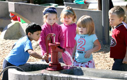 diverse group of children taking turns drinking at an old fashioned red water pump