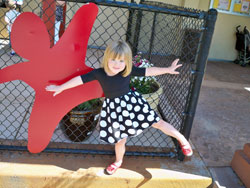 Olivia Grace: little white girl in a dancing pose in front of larger-than-life 2d red metal sculpture in the shape of a symbol for a child