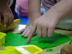 close up of white child's hands playing with green play-doh